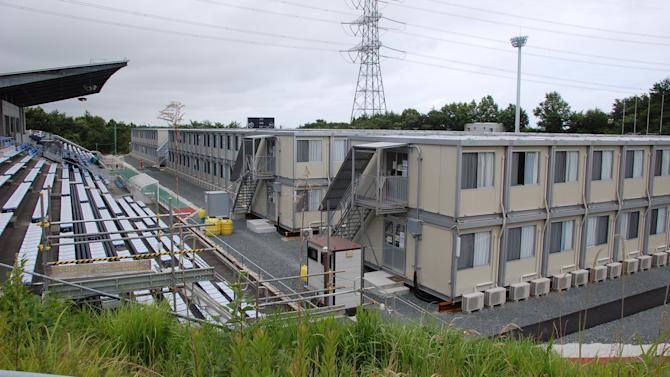 In this July 21, 2012 photo, a prefab houses are built on the football pitch at J-Village national soccer training facility for workers at the Fukushima Dai-ichi nuclear power plant in Naraha, Fukushima Prefecture, northeastern Japan. A growing number of Japanese workers who are risking their health to shut down the crippled Fukushima Dai-ichi nuclear power plant are suffering from depression, anxiety about the future and a loss of motivation, say two doctors who visit them regularly. (AP Photo/Malcolm Foster)