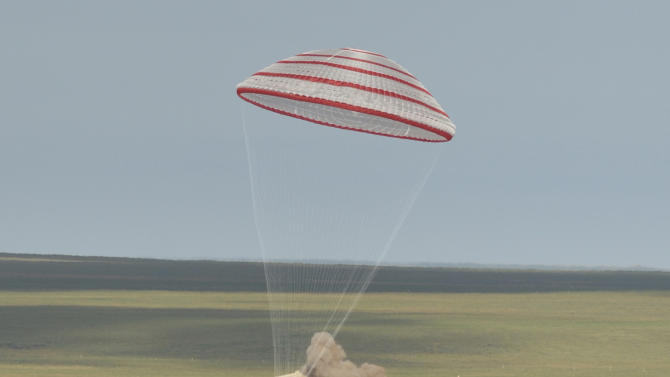 In this photo released by China's Xinhua News Agency, the re-entry capsule of China's Shenzhou 10 spacecraft lands in Siziwang Banner, north China's Inner Mongolia Autonomous Region on Wednesday, June 26, 2013. The space capsule with three astronauts has safely landed on grasslands in northern China after a 15-day trip to the country's prototype space station. (AP Photo/Xinhua,Ren Junchuan) NO SALES