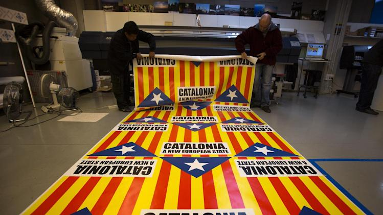 """In this photo taken on Tuesday, Nov. 13, 2012, operators prepare flags for sale that combine the slogan of EU aspiration with the red-and-yellow stripes, blue triangle and white star of the """"estelada"""" flag that symbolizes Catalonia's independence drive in a printing shop in Girona, Spain. Catalonia holds elections on Sunday that will be seen as a test of the regional government's plans to hold a referendum on independence, and one of the key issues emerging is the theoretical place of a free Catalonia in Europe. (AP Photo/Emilio Morenatti)"""