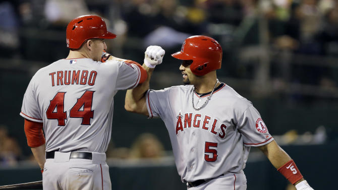 Los Angeles Angels' Albert Pujols (5) celebrates his solo home run with teammate Mark Trumbo (44) against the Oakland Athletics during the seventh inning of a baseball game on Monday, April 29, 2013 in Oakland. Calif. (AP Photo/Marcio Jose Sanchez)