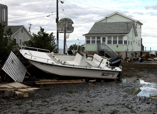 A boat tossed into a neighborhood in the wake of superstorm Sandy on Wednesday, Oct. 31, 2012, in Cedar Bonnet Island, N.J. Power is still out and residents who evacuated the island are still not bein