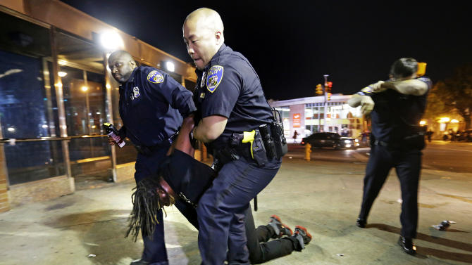 Police carry a man after he was arrested and hit with pepper spray as officers enforced a 10 p.m. curfew, Saturday, May 2, 2015, in Baltimore. (AP Photo/David Goldman)