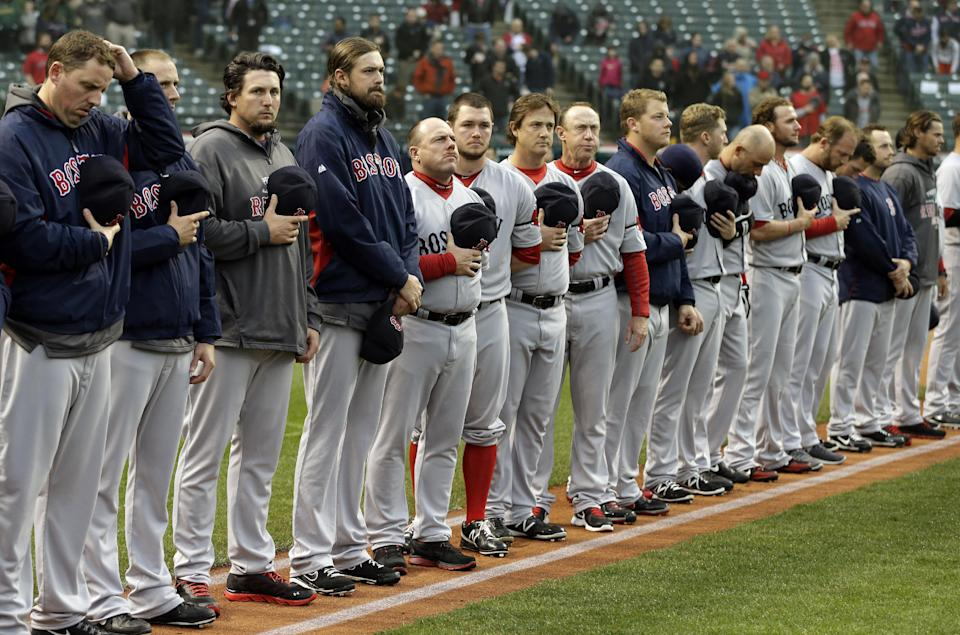 The Boston Red Sox players and coaches observe a moment of silence for the victims of the Boston bombings before a baseball game  against the Cleveland Indians Tuesday, April 16, 2013, in Cleveland. (AP Photo/Mark Duncan)