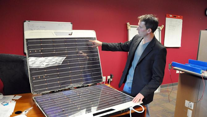 """In this Friday, Sept. 14, 2012 photo, Brian Gramm, chief executive of Peppermint Clean Energy, shows off a protype of the Forty2, in Sioux Falls, S.D. Gramm said the all-in-one """"utility in a box"""" can generate and store enough solar power to run a dorm fridge filled with medicine around the clock in a remote African village. (AP Photo/Dirk Lammers)"""