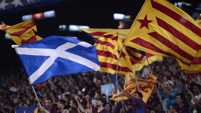 A fan waves a Scottish national flag alongside others waving 'Estelada' flags, that symbolize Catalonia's independence during the Champions League Group F soccer match between Barcelona and Apoel at the Camp Nou stadium in Barcelona, Spain, Wednesday, Sept. 17, 2014. (AP Photo/Manu Fernandez)