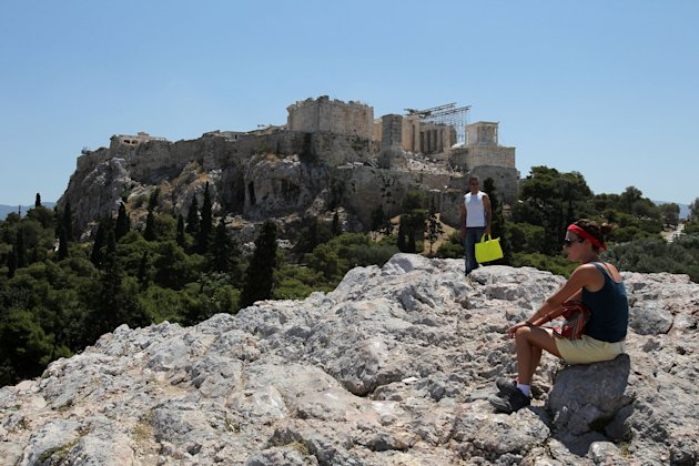 Tourists are seen in front of ancient Acropolis hill in central Athens, on Friday, June 15, 2012. Tourism and shipping are among the pillars Greek economy. Both are under strain amid speculation about whether Greece will have to abandon the euro in a chaotic and possibly economically debilitating exit. (AP Photo/Petros Karadjias)