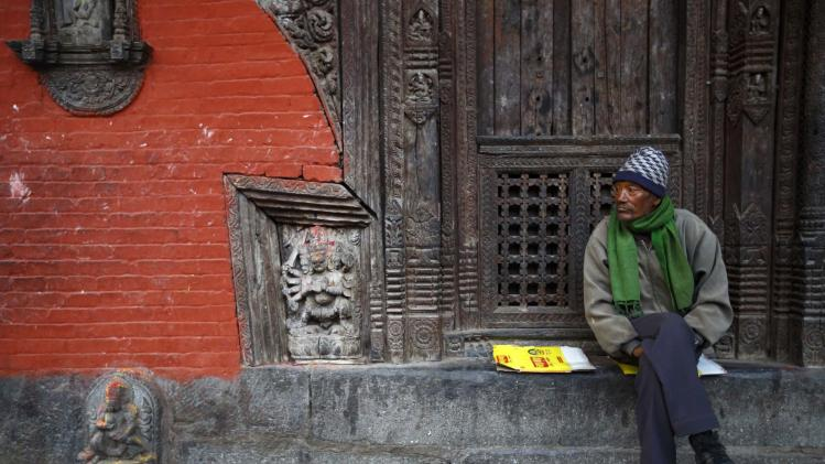A man sits outside a temple in Lalitpur