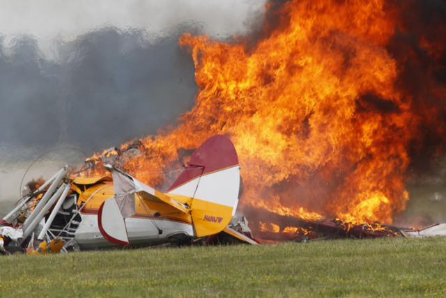 Flames erupt from a plane after it crashed at the Vectren Air Show at the airport in Dayton, Ohio, on Saturday, June 22, 2013. The crash killed the pilot and stunt walker on the plane instantly, authorities said. (AP Photo/Dayton Daily News, Ty Greenlees)