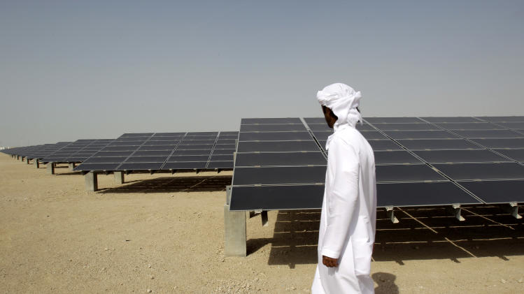 "FILE - In theis Sunday, Jan. 16, 2011 file photo, an Emirati man pass by 10mw photovoltaic plant at Masdar City in Abu Dhabi, United Arab Emirates. The dean of a research institute at the core of Abu Dhabi's green-energy city said Sunday the government remains firmly committed to renewable power after recent shifts in the ambitious project's goals. Masdar City was originally conceived as a self-contained ""carbon-neutral"" community of 40,000 residents and even more commuters where cars would be banned and waste and water would be recycled.(AP Photo/Kamran Jebreili, File)"