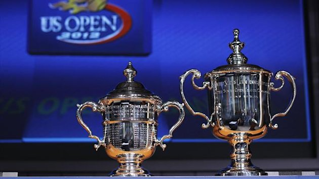 The men's and women's singles trophies rest in front of a television screen during the US Open tournament draw ceremony at the Billie Jean King National Tennis Center in New York August 23, 2012 (Reuters)