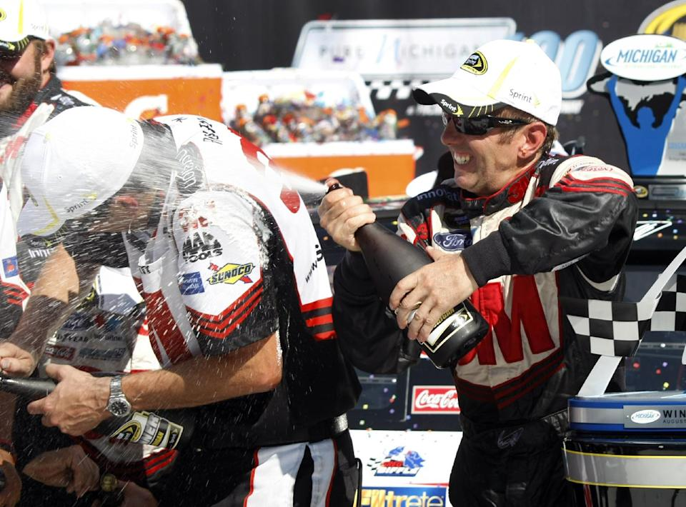 Greg Biffle, right, celebrates his victory by spraying teammates after the NASCAR Sprint Cup Pure Michigan 400 auto race at Michigan International Speedway, Sunday, Aug. 19, 2012, in Brooklyn, Mich. (AP Photo/Bob Brodbeck)