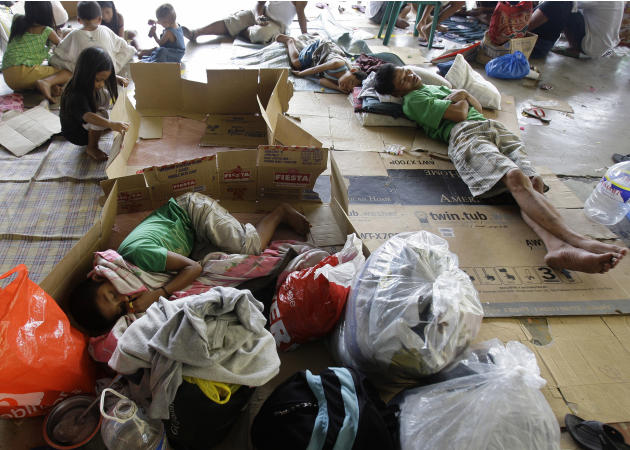 Filipinos sleep on cardboard boxes at an evacuation center in Marikina city, east of Manila, Philippines on Sunday June 26, 2011. At least one person drowned and 17 others remained missing due to Trop