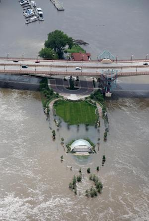In a Friday June 27, 2014 photo, the bandshell near Harriet Island in St. Paul, Minn, is surrounded by flood waters from the Mississippi River. Minnesota communities are trying to bounce back from last month's flooding as damage estimates continue to rise. (AP Photo/The Star Tribune,Kyndell Harkness) MANDATORY CREDIT; ST. PAUL PIONEER PRESS OUT; MAGS OUT; TWIN CITIES TV OUT