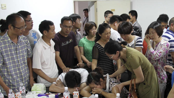 Parents of Wang Linjia, center, are comforted by parents of some other students who were on the Asiana Airlines Flight 214 that crashed at San Francisco International Airport, at Jiangshan Middle School in Jiangshan city, in eastern China's Zhejiang province, Sunday July 7, 2013. Chinese state media have identified the two people who died in the plane crash at San Francisco International Airport on Saturday as Ye Mengyuan and Wang Linjia, students at Jiangshan Middle School in China's eastern Zhejiang province. (AP Photo) CHINA OUT