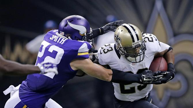 Minnesota Vikings free safety Harrison Smith (22) tries to tackle New Orleans Saints running back Pierre Thomas (23) in the first half of an NFL football game in New Orleans, Sunday, Sept. 21, 2014. (AP Photo/Bill Haber)