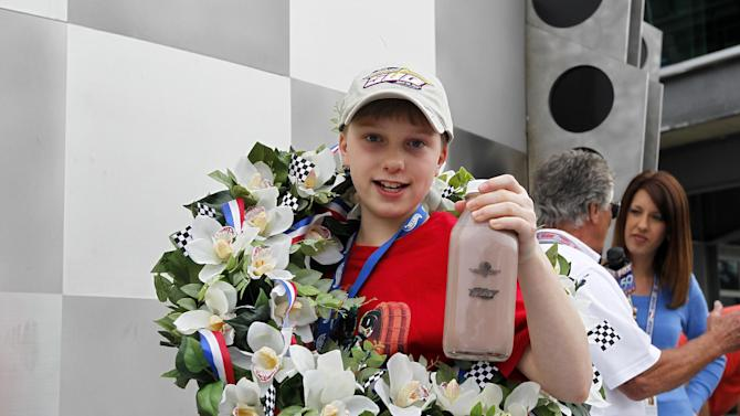 """IMAGE DISTRIBUTED FOR HOT WHEELS - Christopher Bienusa, 12-year-old from Alexandria, Minn., celebrates winning the Hot Wheels """"World's Best Driver Championship"""" in traditional Indy 500 fashion on Saturday, May 25, 2013, at the Indianapolis Motor Speedway. Coached by racing legends Mario and John Andretti, Bienusa's toy-sized car finished first on the world record-setting one mile-long iconic Hot Wheels orange toy track.(Photo by Phil Abbott/Invision for Hot Wheels/AP Images)"""