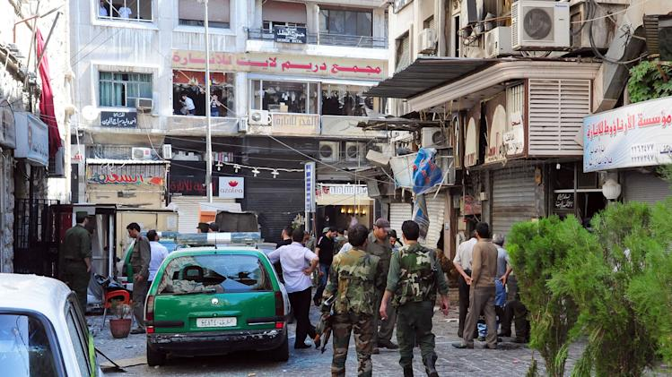 In this photo released by the Syrian official news agency SANA, Syrian army soldiers stand guard at a scene of two explosions in the central district of Marjeh, Damascus, Syria, Tuesday, June 11, 2013. Two explosions hit a central Damascus square Tuesday, killing and wounding dozens of people, activists and the state media reported. State TV said the blasts were caused by suicide bombers, while activists said they were bombs planted there in advance. (AP Photo/SANA)