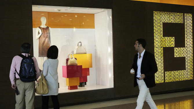 Shoppers look at the window display of a Fendi store Wednesday, June 13, 2012, in Shanghai, China. Chinese consumers can afford to splash out more on higher quality products, but also expect better value for money than in the past, according to a study by the American Chamber of Commerce. (AP Photo/Eugene Hoshiko)