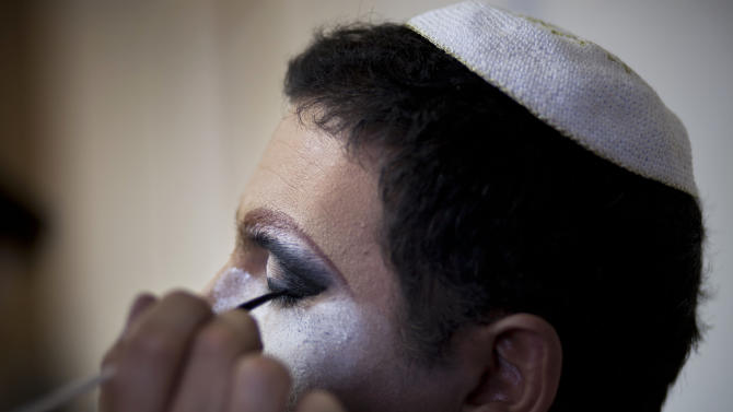 In this photo taken on Tuesday, June 18, 2013, Israeli Orthodox Jew Shahar Hadar has his makeup applied as he prepares for a show at a drag queen school in downtown Tel Aviv, Israel. Hadar, a telemarketer by day, has taken the gay Orthodox struggle from the synagogue to the stage, beginning to perform as one of Israel's few religious drag queens. His drag persona is that of a rebbetzin, a female rabbinic advisor, a wholesome guise that stands out among the sarcastic and raunchy cast of characters on Israel's drag queen circuit. (AP Photo/Oded Balilty)