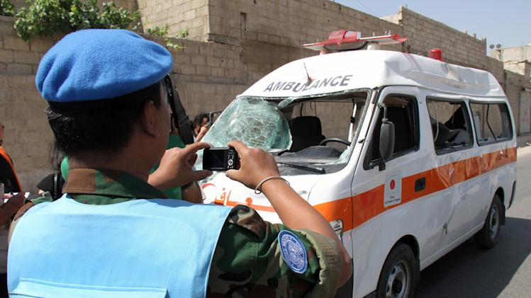 A UN observer photographs an ambulance that was destroyed after a car bomb exploded near the shrine of Sayyida Zeinab, in a suburb of Damascus, Syria, Thursday June 14, 2012. A car bomb exploded Thursday in a Damascus suburb that is home to a popular Shiite Muslim shrine, wounding at least two people, Syria's state-run news agency SANA reported, while activists said regime troops continued shelling rebellious areas in central Homs province. (AP Photo/Bassem Tellawi)