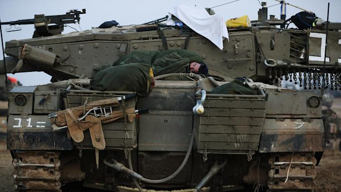 An Israeli soldier sleeps on a tank at a staging area near the Israel Gaza Strip Border, southern Israel, early Tuesday, Nov. 20, 2012. On Tuesday, grieving Gazans were burying militants and civilians killed in ongoing Israeli airstrikes, and barrages of rockets from Gaza sent terrified Israelis scurrying to take cover. Efforts to end a week-old convulsion of Israeli-Palestinian violence drew in the world's top diplomats Tuesday, with U.S. President Barack Obama dispatching his secretary of state to the region on an emergency mission and the U.N. chief appealing from Cairo for an immediate cease-fire. (AP Photo/Lefteris Pitarakis)