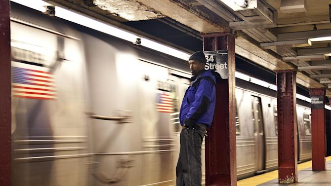 A commuter waits as the first A train approaches the platform at Penn Station as MTA resumed limited service Thursday, Nov. 1, 2012, in New York. The decision to reopen undamaged parts of the nation's largest transit system came as the region struggles to restore other basic services to recover from a storm that ravaged the East Coast, killing more than 70 people and leaving millions powerless. (AP Photo/CX Matiash)