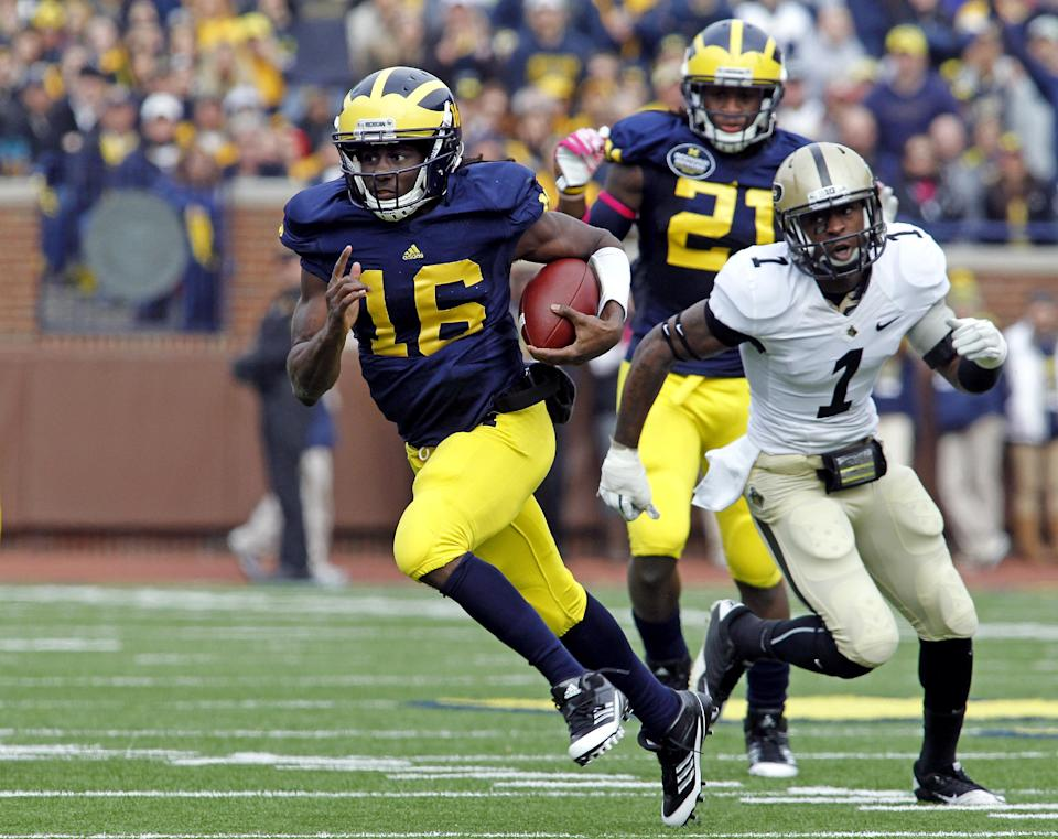 Michigan quarterback Denard Robinson (16), pursued by Purdue cornerback Normondo Harris (1), rushes for a first down in the second quarter of an NCAA college football game, Saturday, Oct. 29, 2011, in Ann Arbor, Mich. (AP Photo/Tony Ding)