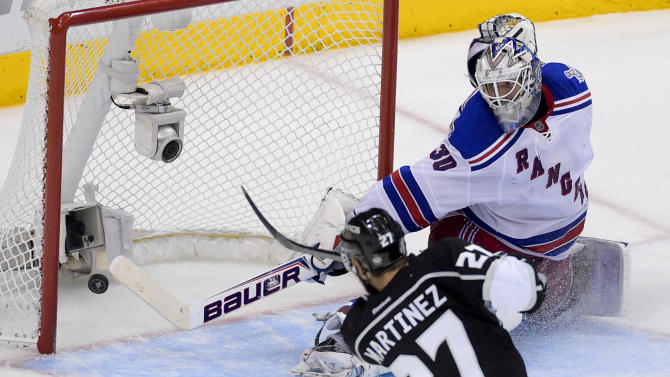 Los Angeles Kings defenseman Alec Martinez, left, scores the winning goal past New York Rangers goalie Henrik Lundqvist, of Sweden, during the second overtime period in Game 5 of an NHL hockey Stanley Cup finals, Friday, June 13, 2014, in Los Angeles