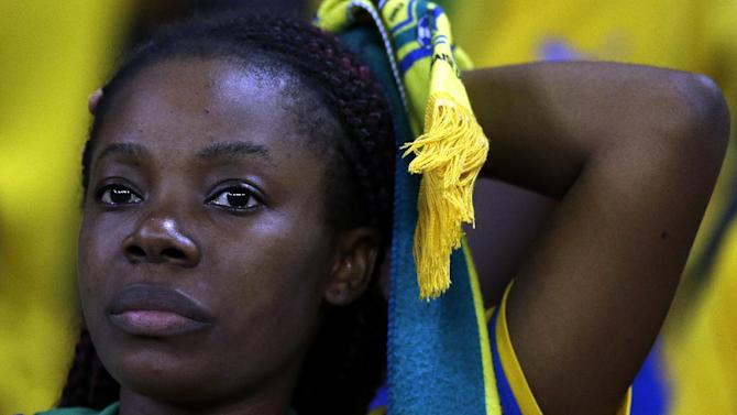 A Gabon soccer fan is dejected after her national team was defeated during their African Cup of Nations Group A soccer match by Equatorial Guinea in Bata, Equatorial Guinea, Sunday, Jan. 25, 2015. (AP Photo/Themba Hadebe)