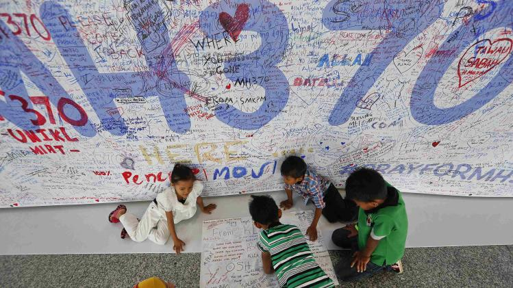 Children write messages of hope and support for the passengers of the missing Malaysia Airlines MH370 at the departure hall of Kuala Lumpur International Airport