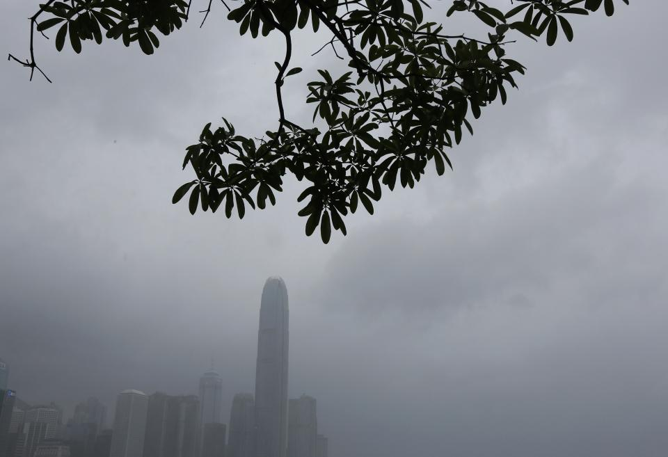 Clouds are hanging low with rain over Hong Kong's central business center near the waterfront in Hong Kong Wednesday, Aug. 14, 2013. Typhoon Utor lashed Hong Kong with wind and rain, closing down the bustling Asian financial center Wednesday before sweeping toward mainland China. (AP Photo/Vincent Yu)