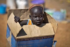 A displaced boy carries a cardboard box inside a United …