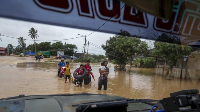 People carry their belongings as they evacuate through a flooded street on the outskirt of Kota Bharu in Kelantan