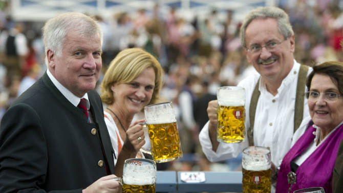 "Bavarian Prime Minister Horst Seehofer, his wife Karin, Munich's Mayor Christian Ude and his wife Edith Welser-Ude toast with their beer mugs during the opening ceremony of the famous Bavarian ""Oktoberfest"" beer festival in Munich, southern Germany, Saturday, Sept. 22, 2012. The world's largest beer festival, to be held from Sept. 22 to Oct. 7, 2012 will see some million visitors. (AP photo/dapd, Lennart Preiss)"