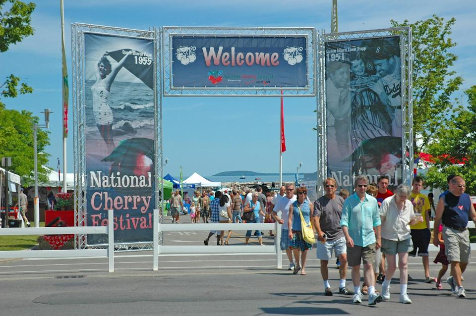 In this undated photo provided by the Traverse City Tourism, people enjoy a summer day in the Open Space park by Grand Traverse Bay in Traverse City, Mich. Some local residents say festivals occupy the park too much in summer, while others say it's a reasonable price to pay for a strong tourism economy. (AP Photo/Traverse City Tourism)