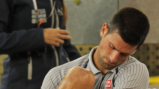 Novak Djokovic from Serbia take out his sock after he got injured during the match against Grigor Dimitrov from Russia at the Madrid Open tennis tournament, in Madrid, Tuesday, May 7, 2013. (AP Photo/Andres Kudacki)