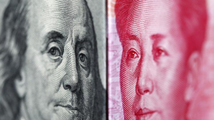 Illustrative file photo of a 100 yuan banknote placed beside a U.S. 100 dollar banknote