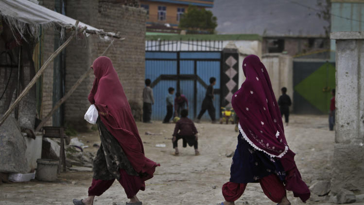 Afghan Kuchi women walk along a road on the outskirts of Kabul, Afghanistan, Monday, April 29, 2013. (AP Photo/Rahmat Gul)