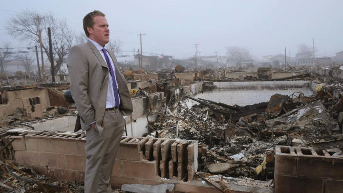 In this Tuesday, Dec. 4, 2012 photo, Patrick Mullaney walks around the remains of his family's home in the Breezy Point section of New York. More than 100 houses in Breezy Point were destroyed by a massive fire during Superstorm Sandy on Oct. 29, 2012. (AP Photo/Mark Lennihan)