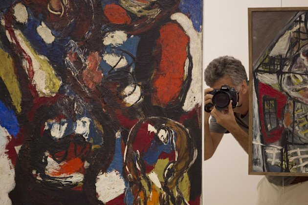 A journalist takes pictures during a media tour of the Rio Art Museum before its inauguration in Rio de Janeiro, Brazil, Thursday, Feb. 28, 2013. The museum, scheduled to open on Friday, is part of Rio's multi-billion dollar bid to reinvent itself before playing host to a double header of mega-events, the 2014 World Cup soccer tournament and the 2016 Olympics. (AP Photo/Silvia Izquierdo)