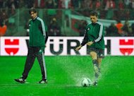 Italian referee Gianluca Rocchi (R) tests the ball on the watercovered pitch at the stadium amid a strong rain before postponing the FIFA 2014 World Cup qualifying football match Poland vs England in Warsaw