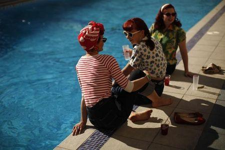 Women, dressed in fifties-style outfits, cool off their feet in a swimming pool during the 19th Rockin' Race Jamboree International Festival in Torremolinos
