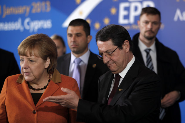 German Chancellor Angela Merkel and Cyprus' main opposition Democratic Rally party leader Nicos Anastasiades, right, are seen before a European People's Party (EEP) meeting in Cyprus' southern coastal