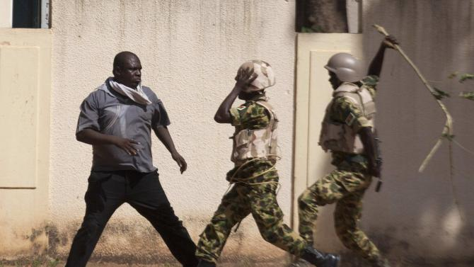 Soldiers hit an anti-government protester with a stick in Ouagadougou