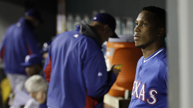Texas Rangers pitcher Pedro Strop, right, stands in the visitors' dugout after he was pulled from a baseball game against the Seattle Mariners in the eighth inning, Tuesday, May 3, 2011, in Seattle. Strop was charged with the loss as the Mariners beat the Rangers, 4-3. (AP Photo/Ted S. Warren)