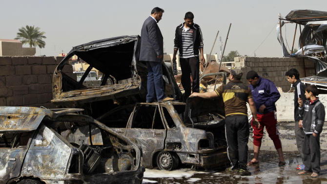 People inspect their destroyed cars at the scene of a car bomb attack in the Ameen neighborhood of eastern Baghdad, Iraq, Sunday, Feb. 17, 2013. A series of car bombs exploded within minutes of each other as Iraqis were out shopping in and around Baghdad on Sunday, killing and wounding scores of people, police said. (AP Photo/ Khalid Mohammed)