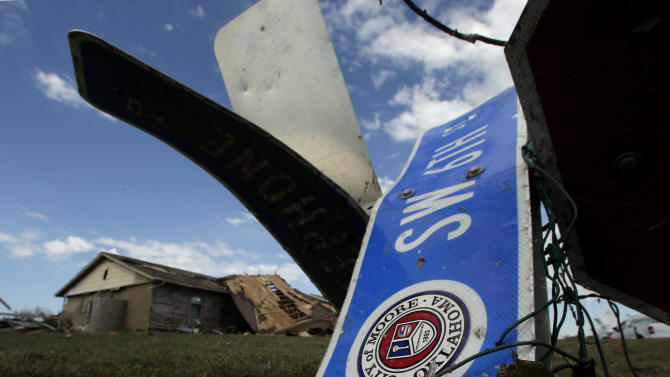 A tornado-ravaged home stands in the distance beyond a twisted street sign Wednesday, May 22, 2013, in Moore, Okla. Cleanup continues two days after a huge tornado roared through the Oklahoma City suburb, flattening a wide swath of homes and businesses. (AP Photo/Charlie Riedel)