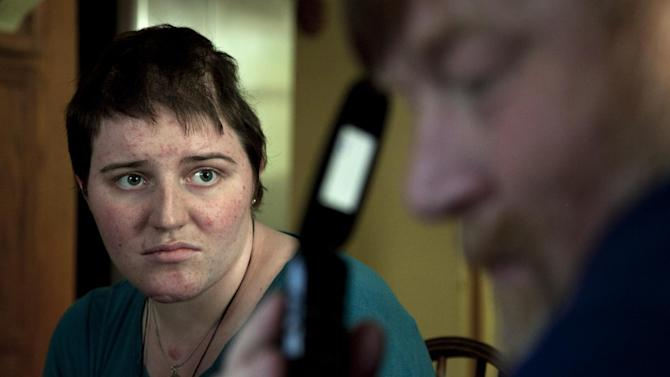 In this Thursday, Aug. 2, 2012 photo, Meg Theriault listens as her father, Todd Theriault, right, calls a pharmacy about her medication at their home in Salisbury, Mass., on the first day she had been home since a serious minivan crash in New Zealand two-and-a-half months earlier. (AP Photo/Steven Senne)