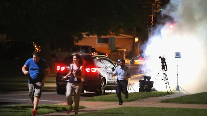 An Al Jazeera television crew, covering demonstrators protesting the shooting death of teenager Michael Brown, scramble for cover as police fire tear gas into their reporting position, in Ferguson, Missouri, on August 13, 2014