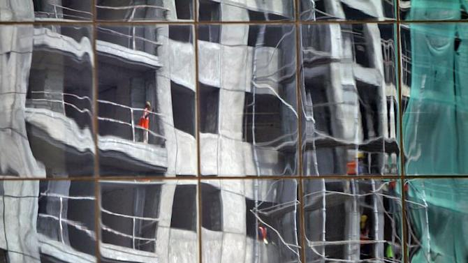 Residential building undergoing construction is reflected on glass facades of a commercial complex in Chennai